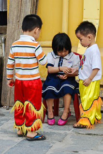 Three Vietnamese children in costume waiting to go on stage.